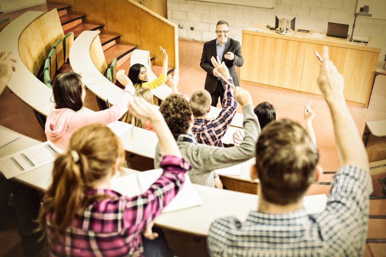 Students raising their hands in a classroom.